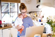 Mother with baby in kitchen looking at laptop — Stock Photo
