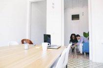 Молодые бизнесмены сидят и работают на диване в офисе — стоковое фото