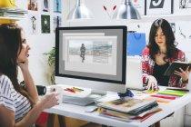 Два модельні жіночі блогерів, сидячи на столі в офісі — стокове фото