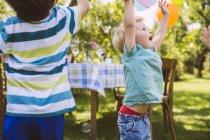 Niños tratando de atrapar burbujas de jabón en el jardín - foto de stock