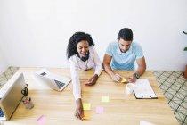 Joven hombre y mujer escribiendo en notas adhesivas en el escritorio en la oficina - foto de stock