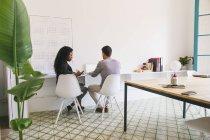Giovani imprenditori utilizzando laptop e smartphone in ufficio moderno — Foto stock