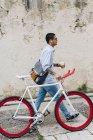 Jeune homme marchant à vélo dans la ville — Photo de stock