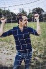 Lachender Mann hinter Fußball Netto — Stockfoto