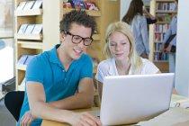 Étudiants avec ordinateur portable apprenant dans une bibliothèque — Photo de stock