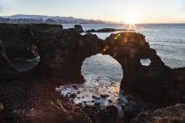 Iceland, Snaefells, Arnarstapi, view to natural arch at backlight — Stock Photo