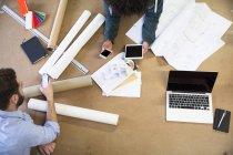 Zwei Kollegen mit tragbaren Geräten umgeben von Bauplänen — Stockfoto