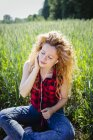 Portrait of woman sitting in a field hearing music with earphones — Stock Photo
