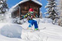 Ragazzo in casco e abbigliamento da sci sciare in giornata soleggiata sul pendio di montagna innevato, capanna di legno su priorità bassa — Foto stock