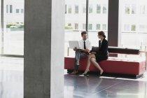 Homme d'affaires et femme d'affaires parlant dans le hall du bureau — Photo de stock