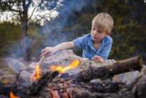 Кавказький хлопчика в табір вогню в парку — стокове фото