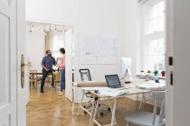 Two creative professionals talking in office — Stock Photo