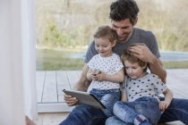 Father and sons sitting on floor using digital tablet — Stock Photo