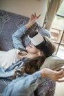 Молода жінка вдома за допомогою віртуальної реальності окуляри — стокове фото
