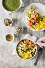 Smoothie bowl with mango, papaya, kiwi, banana, pear and toppings with person hand — Stock Photo