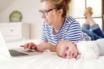 Madre con bambino sdraiato sul letto a lavorare con il computer portatile — Foto stock