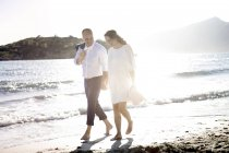 Pregnant woman and man walking on beach — Stock Photo