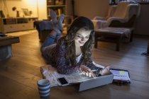 Mujer joven en casa trabajando con tableta digital - foto de stock