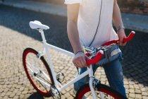Женщина, толкая велосипедов на булыжной мостовой — стоковое фото
