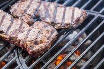 Biftecks de boeuf grillés au charbon de bois sur barbecue — Photo de stock