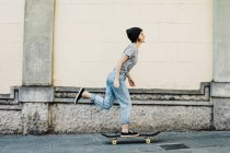 Young female skate boarder riding her skateboard — Stock Photo