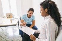 Jungunternehmer und Frau diskutieren Papiere im Büro — Stockfoto