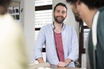 Professionnels de la création souriants parlant au bureau — Photo de stock