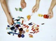 Mãos femininas com utensílios de costura no fundo branco — Fotografia de Stock