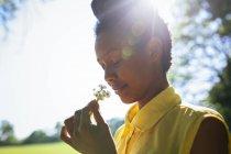 Retrato de sorrir jovem mulher cheirando flores — Fotografia de Stock