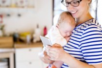 Mother holding little baby looking at cell phone — Stock Photo