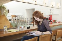 Junge Frau sitzt im Café und betrachtet Ausdrucke — Stockfoto