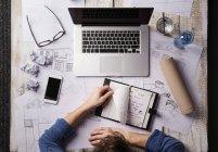 Архитектор, работающий за рабочим столом с ноутбуком, смотрит на персонального организатора — стоковое фото