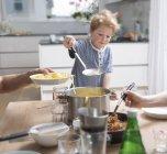 Niño orgulloso servir la pasta en la cocina - foto de stock