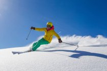 Woman skiing on snowy mountain slope in bright skiwear, helmet and googles — Stock Photo
