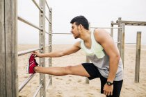 Young man stretching on wall bars on beach — Stock Photo