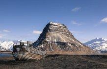 Ісландія, півострів Snaefellsnes, Grundafjoerdur, Kirkjufell, старий човен проти пагорбі над водою — стокове фото