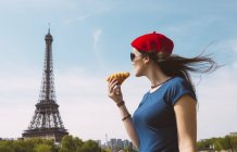 France, Paris, woman holding croissantlooking at Eiffel Tower — Stock Photo