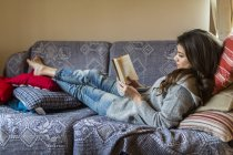 Young woman at home reading a book — Stock Photo