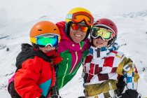 Portrait of smiling female skier and sons in ski resort — Stock Photo