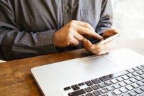 Businessmann usando smartphone y laptop, primer plano - foto de stock