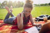 Femme allongée sur une couverture sur une prairie téléphoner avec smartphone — Photo de stock