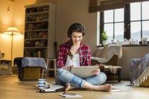 Jeune femme à la maison travaillant avec une tablette numérique — Photo de stock