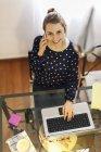 Молода жінка працює з ноутбуком вдома. — стокове фото
