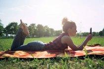 Femme avec smartphone allongé sur la couverture sur une prairie — Photo de stock