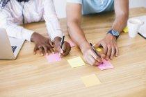 Mann und Frau auf selbstklebende Hinweise am Schreibtisch im Büro schreiben — Stockfoto