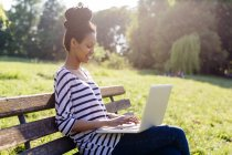 Young woman sitting on park bench using laptop — Stock Photo