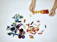 Женские руки сортировки швейных принадлежностей на белом фоне — стоковое фото