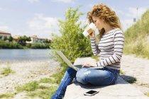 Mujer bebiendo café para ir mientras usa el ordenador portátil a orillas del río - foto de stock