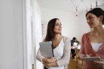 Dos mujeres hablando en la oficina con el hombre trabajando en segundo plano - foto de stock