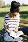 Jeune femme assise sur le banc de parc, lisant un livre — Photo de stock